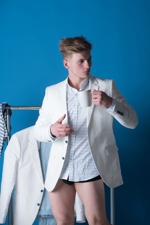 Macho in shirt, jacket and underpants drinking from cup. Man with muscular legs in dressing room. Clothes rack on blue background. Fashion and underwear concept