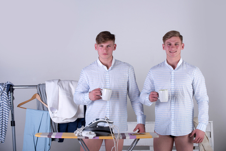 Men with cups standing in blue shirts and underpants. Two brothers with serious and happy smiling faces on grey background. Dressing room with clothes rack and ironing board with iron. Fashion concept