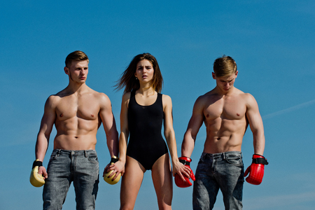 Woman and twins with muscular body. Men and coach sunny outdoor on blue sky. Boxer workout and healthy fitness. Sport people or team work. Winner and loser in boxing gloves with girl.