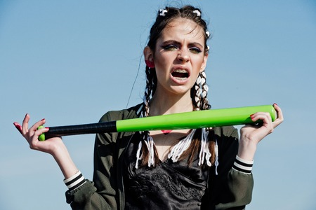 Woman with baseball bat. Sport or criminal girl outdoor. Hooligan on blue sky. Beauty and fashion. Bandit gang and conflict. Reklamní fotografie - 83332455