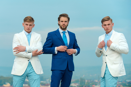Businessman with bodyguards. Security service concept. Men posing on blue sky. Group of business people wearing formal suits. Boss and employees on sunny day. Stock Photo