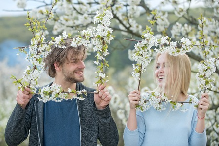 Man and woman in spring. Couple in love in blossoming flower. Girl and happy guy cherry bloom frame. Spa and relaxation. Nature and environment. Stock Photo