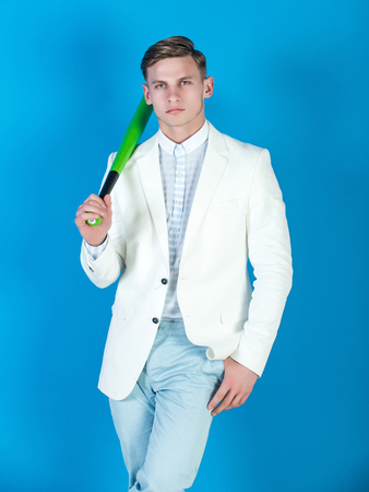 Man holding green bat. Businessman wearing white jacket, shirt and pants. Baseball player posing on blue background. Fashion and sport. Power and energy concept. Zdjęcie Seryjne