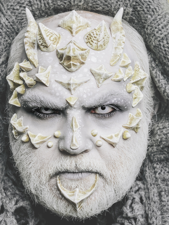 horror man or monster with horns or thorns on face with futuristic makeup of guy alien with beard and lens in eyes Stock Photo