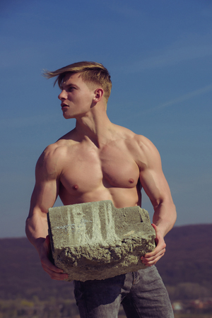 Athletic bodybuilder as hercules. Sport and workout. Gladiator or atlant. Man builder with muscular body. Adam hold bog stone. Stock Photo