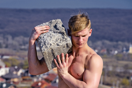 Adam hold bog stone. Sport and workout. Athletic bodybuilder as hercules. Gladiator or atlant. Man builder with muscular body. Stock Photo