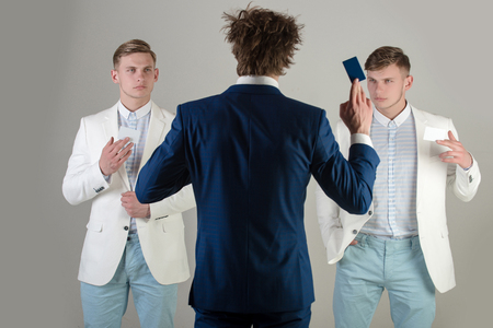 Man wearing blue jacket, back view. Information and cooperation. Business ethics concept. Businessmen exchanging cards on grey background. Group of people facing each other. Фото со стока