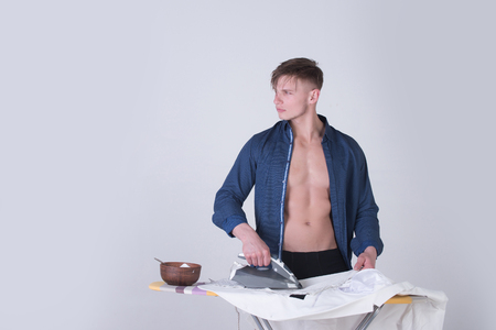 Macho in blue shirt with sexy torso ironing clothes with iron on grey background. Bowl with food for healthy dieting. Housework concept, copy space