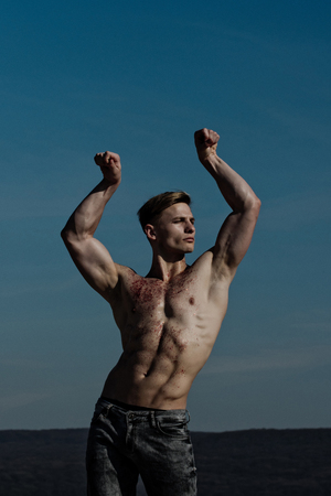 Adam with glitter on bare chest. Sport and workout. Athletic bodybuilder pose as hercules. Gladiator or atlant. Man with muscular wet body.