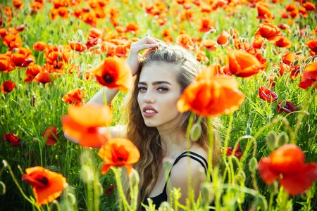 poppy seed. girl with long curly hair in red flower field with green stem on natural background, summer, spring, drug and love intoxication, opium