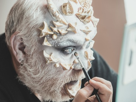 Actor applying make up on face. Fantasy and art. Theatre and cinema concept. Senior male model in backstage. Man with makeup brush. 版權商用圖片