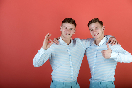 Two brothers showing thumbs up and ok gestures. Models smiling on red background. Happy men hugging. Twins wearing blue shirts. Family, brotherhood and friendship concept.