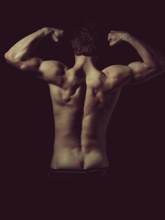 guy with sexy muscular body and back posing as bodybuilder showing biceps and triceps isolated on white background