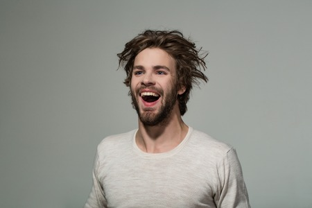 happy man with long stylish uncombed hair and smiling bearded man on grey background, morning and barbershop fashion