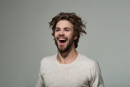 homme heureux avec des cheveux long et non coiffé élégant et souriant homme barbu sur fond gris, la mode du matin et le salon de coiffure
