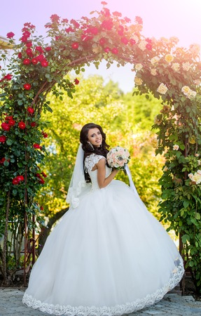 Bride with long brunette hair with flower. Wedding holiday celebration at red floral arch. Beauty and fashion. Girl smile with fashionable makeup in earring. Woman with dress and veil at rose bouquet.