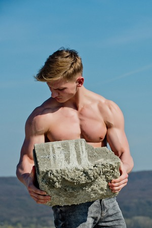 Adam hold bog stone. Athletic bodybuilder as hercules. Gladiator or atlant. Sport and workout. Man builder with muscular body. Stock Photo