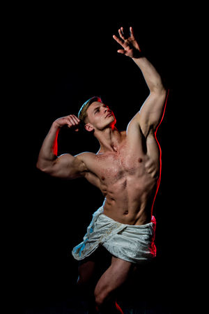 Athletic bodybuilder pose as statue. Adam with glitter on bare chest. Sport and workout. Gladiator or greek god. Man with muscular wet body in white fascia.