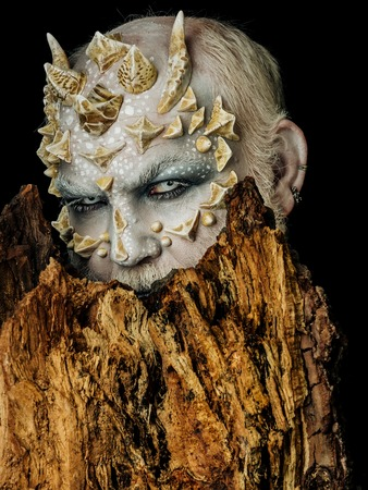 creepy alien: Tree spirit and fantasy concept. Monster with sharp thorns and warts. Druid behind old bark on black background. Man with dragon skin and bearded face. Goblin with horns on head. Stock Photo