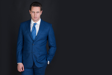 Man, confident businessman or handsome manager with fashionable hair, haircut posing in stylish blue formal suit, white shirt and tie on grey background. Business fashion, copy space Banco de Imagens