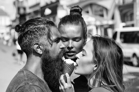 man hipster with bearded handsome face and two pretty girls eating tasty ice creame cornet together on city street background outdoor closeup