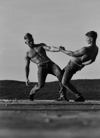 men or bodybuilders, athletes with sexy, muscular torsos with six packs, abs, biceps, triceps wrestling outdoor in mountains on sky, black and white
