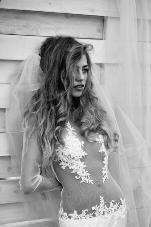 woman with long hair in wedding dress and bride veil on wooden background, black and white