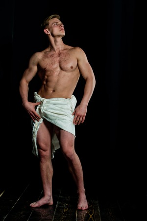 Man with muscular wet body in white fascia. Adam with glitter on bare chest. Athletic bodybuilder pose as statue. Sport and workout. Gladiator or greek god. Stock Photo