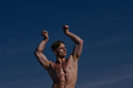 Adam with glitter on bare chest. Man with muscular wet body. Sport and workout. Athletic bodybuilder pose as hercules. Gladiator or atlant.