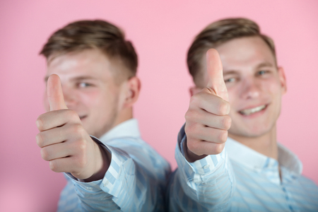 Two thumbs up hand gestures with blurred men happy smiling on pink background. Like and approval concept. Body language