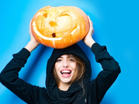 Halloween woman with happy face. Party and traditional food. Woman in jersey and hood at blue wall. Girl with orange scary pumpkin in wig. Holiday and celebration. Stock Photo