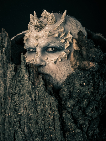 man or monster with thorns on face with futuristic makeup as alien with beard and lens in eyes on black background near tree Stock Photo