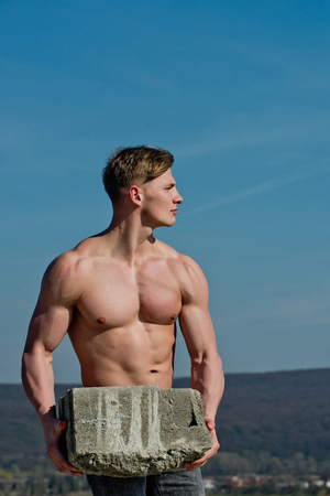 Adam hold bog stone. Man builder with muscular body. Sport and workout. Athletic bodybuilder as hercules. Gladiator or atlant.