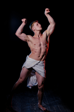 Adam with glitter on bare chest. Man with muscular wet body in white fascia. Sport and workout. Athletic bodybuilder pose as statue. Gladiator or greek god.