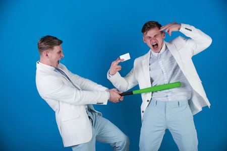 Businessman batting rival with baseball bat. Man showing finger gun with blank card. Managers shouting and fighting on blue background. By force or persuasion. Business negotiations concept.