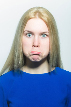 Girl puffing cheeks on funny face. Young woman with crossed grey eyes, healthy skin and long blond hair in blue dress isolated on white. Grimace and facial expression.