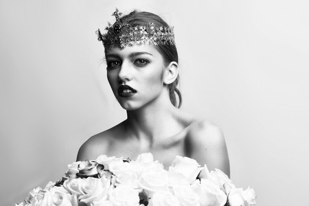 queen woman with luxury crown with diamond and gem has bare shoulders hold rose bouquet, black and white