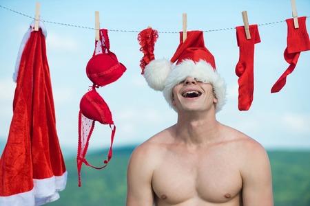 Kerstman met gelukkige gezicht en spierkist draag kerstmuts in de buurt van rode jas, sok, bh, shorts en garter zomer buiten op blauwe hemelachtergrond