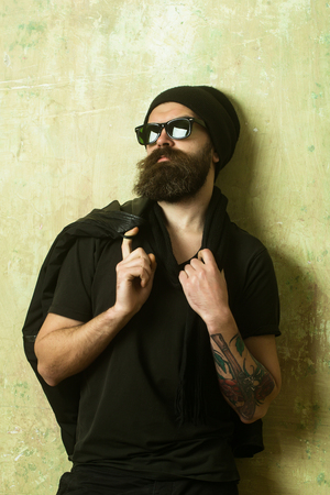 barbershop: biker or hipster man in glasses, hat and shirt with leather jacket on textured wall background, guy has long beard and mustache