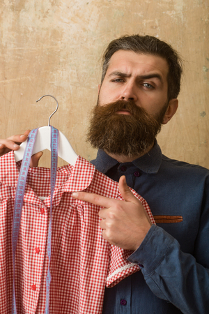 Shopping and black Friday. Tailor guy in workshop. Man with beard hold dress and tape measure. Designer with measuring tape. Beauty and fashion. Stock Photo