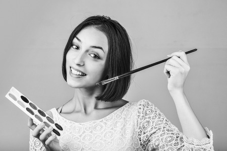 girl with short hair in tracery blouse with paint and long paintbrush smiling, black and white