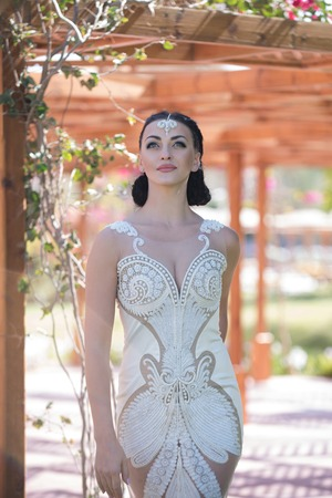Woman with fashion makeup on young pretty face brunette in white lace wedding elegant vintage dress with jewelry decoration on her forehead posing on wooden blur background outdoor Stock Photo