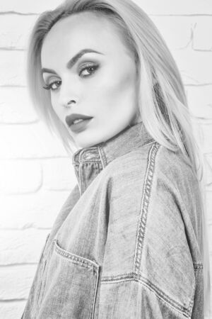 woman, fashion model with blond hair and red lips in sexy denim blue jeans clothes poses on white brick wall, black and white