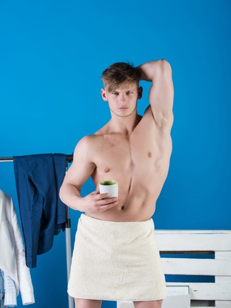 Athlete showing muscular torso. Clothes rack on blue background. Macho wrapped in white towel. Health and fitness concept. Man posing with cup.