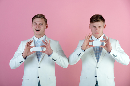 Men with serious and happy faces holding blank cards. Banking and saving concept. Businessmen wearing white jackets on pink background. Cooperation and partnership. Business communication and meeting. Stock Photo