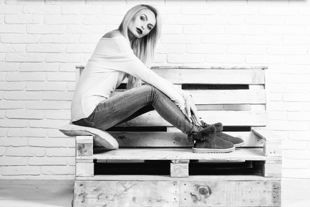 woman sexy fashion model with blond hair in jeans casual clothes sits on wooden pallet sofa on brick wall, black and white