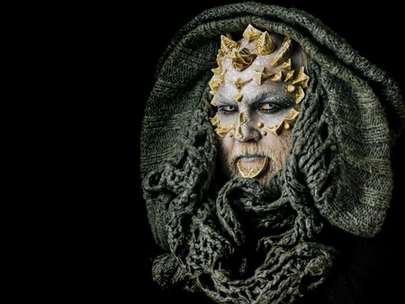 Monster face with white eyes, thorns and warts. Alien or sorcerer makeup. Demon head with grey hood isolated on black. Horror and fantasy concept. Man with dragon skin and beard, copy space