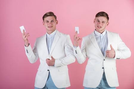 空白のカードの上に親指を表示の男性はピンク色です。銀行とコンセプトを保存します。ビジネス コミュニケーションと会議。白のジャケットを身