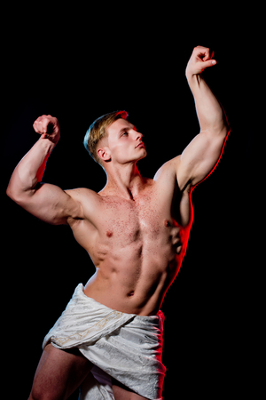 Gladiator or greek god. Athletic bodybuilder pose as statue. Man with muscular wet body in white fascia. Sport and workout. Adam with glitter on bare chest.