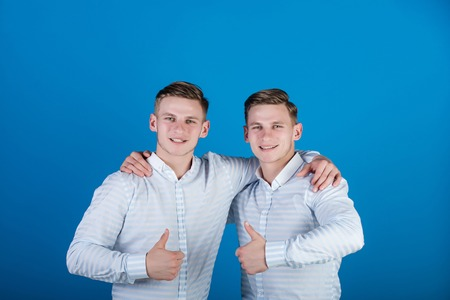 Happy men hugging and showing thumbs up gestures. Twins wearing striped shirts. Models standing together. Family, brotherhood and friendship concept. Two brothers smiling on blue background.